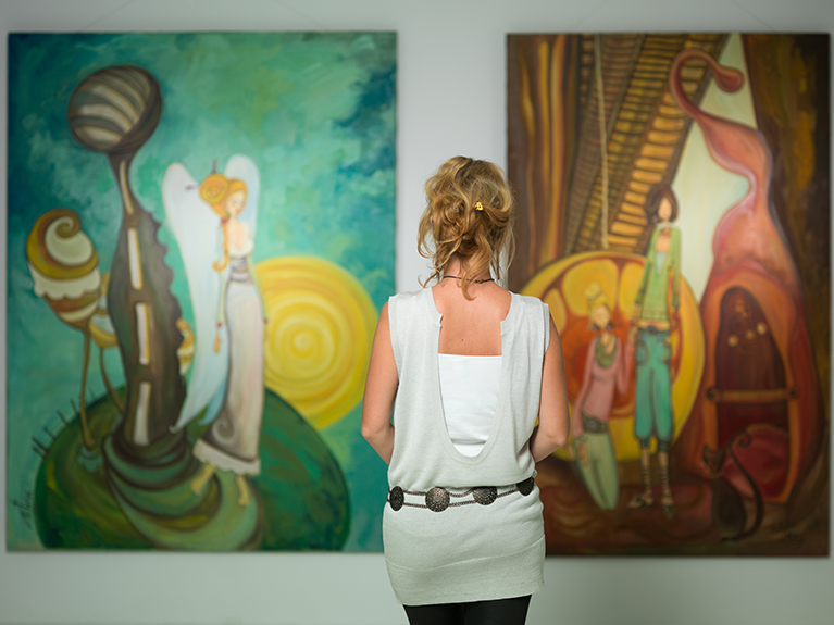A woman looking at two paintings on a wall