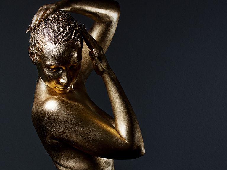 A woman posing as a gold statue