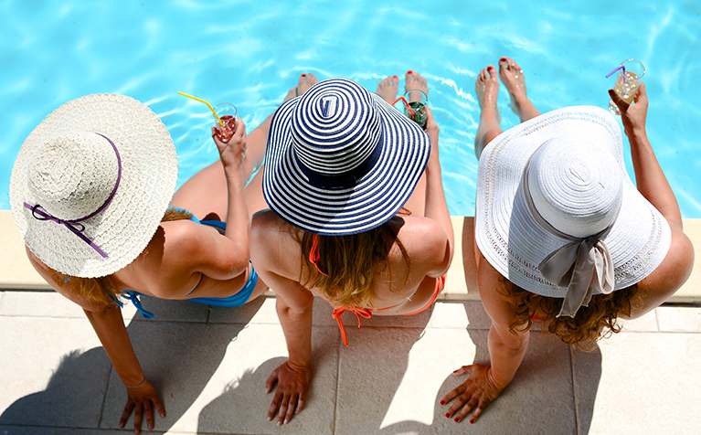 Three travelers sitting by the pool.