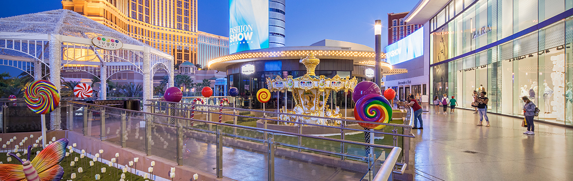 At Fashion Show in Las Vegas, an outdoor walkway is decorated by large lollipops, outdoor carousel.