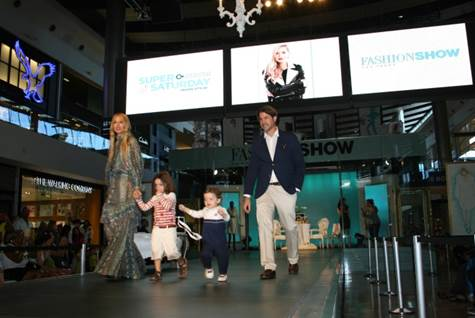 A family walks the runway stage holding hands