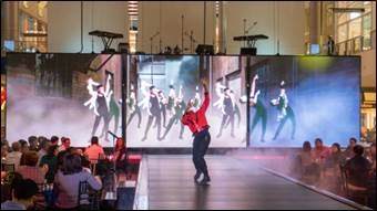 Man dancing on a runway stage with displays behind him
