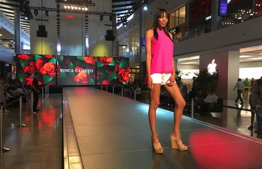 A woman model walking a runway in a fashion show in a pink top and white shorts