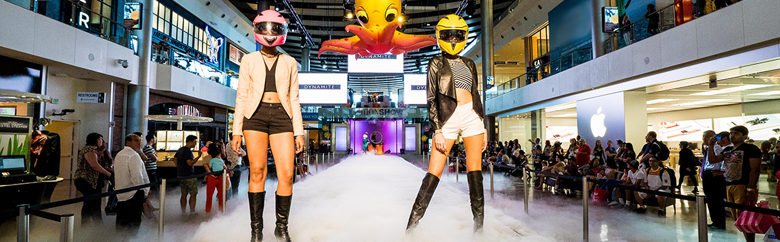 Two models walking a lit up runway in with fashionable helmets